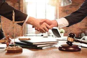bigstock-Lawyer-And-His-Client-Handshak-325228753